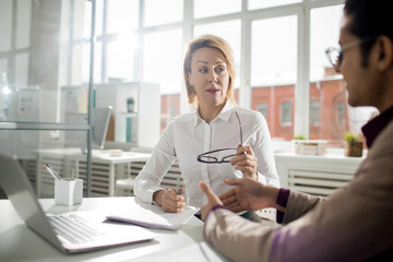 Mature businesswoman discussing with male colleague in office