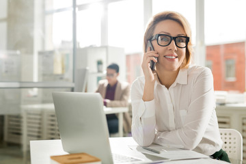 Smiling businesswoman talking on the phone at her workplace