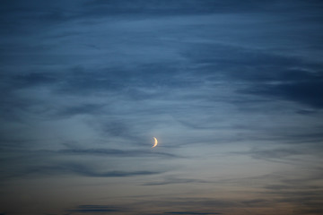 blue evening sky background with half moon sickle sky contours and clouds. fairytale sky at dusk with romantic mood