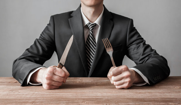 Businessman holding fork with knife and ready to eat. Concept of competition in business