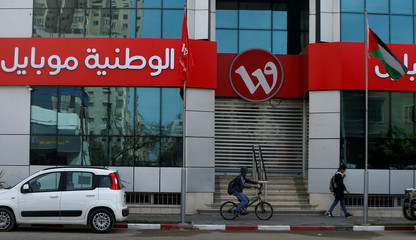 Palestinian boy rides his bicycle past the closed building of Wataniya Mobile company in Gaza City