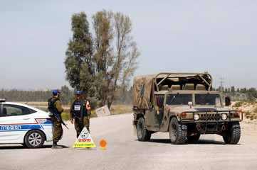 Israeli military vehicles block a road near the border between Israel and the Gaza Strip
