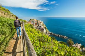 Woman hiking on the path in vineyard near Manarola village. Cinque Terre. Liguria, Italy.