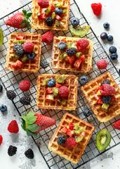 Fresh egg waffles dessert for breakfast with fruits strawberries, blueberries, blackberries, raspberries and kiwi