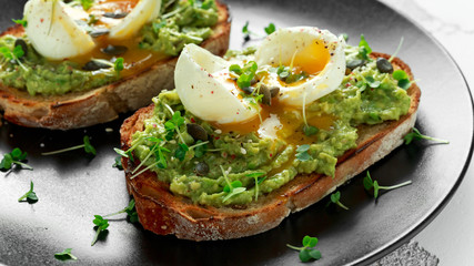 Healthy avocado and egg toasts with pumpkin and sesame seeds, sprinkled with cress salad