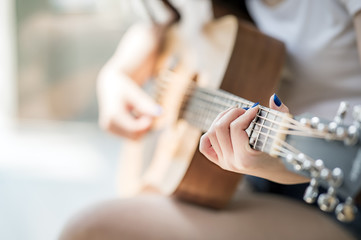 woman hands playing acoustic guitar