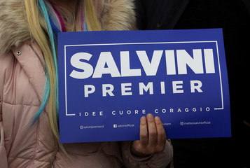 A woman holds a placard supporting Northern League's leader Matteo Salvini as he arrives for a meeting in Milan