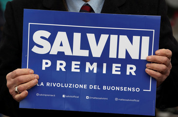A man holds a placard supporting Northern League's leader Matteo Salvini as he arrives for a meeting in Milan