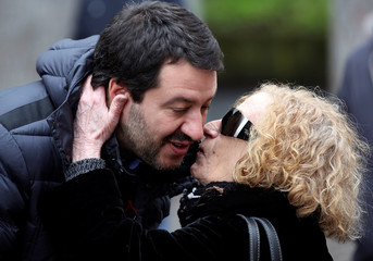 A woman kisses Northern League's leader Matteo Salvini as he arrives for a meeting in Milan