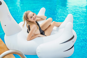 Sexy Girl in black swimming suit lying on the inflatable mattress in the swimming pool . woman smile in bikini on white swan pool float