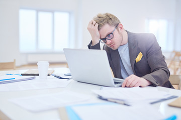Puzzled young manager sitting by table in front of laptop and reading online data or statistics