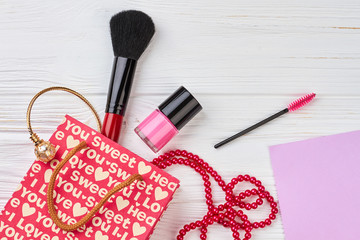 Gift bag and beauty accessories. Flat lay of shopping bag open out with cosmetics and jewelry, blank paper card.