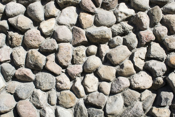 Texture laid out of stone, a wall made of stones on a cement solution