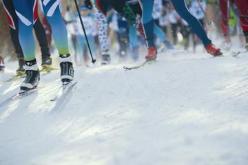 Ski marathon - de-focused view of many legs of sportsmen running on snow Wall mural