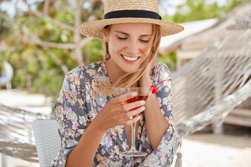 Lovely happy woman wears straw hats and flower printed blouse, recreats alone outdoor during summer shining weather, drinks cold fresh cocktail, pleased after lying in hammock. Recreation time