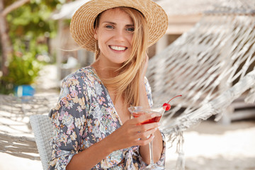Pretty glad young woman with shining smile, wears straw hat and blouse, holds cocktail in hands, rests outdoor near hammock, spends summer vacation in tropical hot country. Seasonal recreation