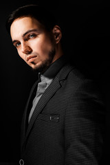 Portrait of young and handsome businessman holding a jacket isolated on black background. Portrait of handsome business man in suit on black background. Studio fashion portrait.