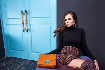 Beautiful sexy lady long brunet hair spring autumn collection fashion clothes for date party success business woman wear skirt black sweater shoes sit on sofa room interior luxury style accessory bag.