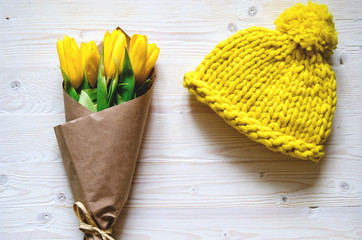 A yellow knitted cap of thick Merino yarn. Nearby is a bouquet of yellow tulips wrapped in paper.