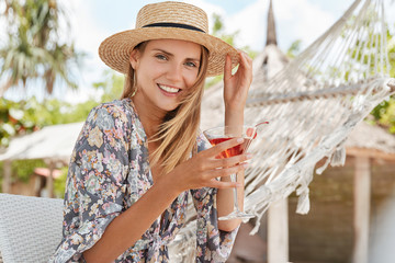 Pretty young female wears summer hat, holds glass of cocktail, has happy expression and pleasant look, sits against hammock on chair outdoor, breathes freh air and enjoys sunny weather. Rest time