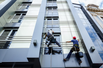 Team of industrial climbers at work, they are washing building facade