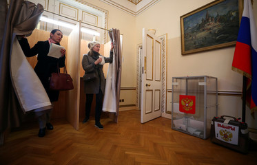 People walk out of a voting booth,during the presidential election, inside the Russian Embassy in London