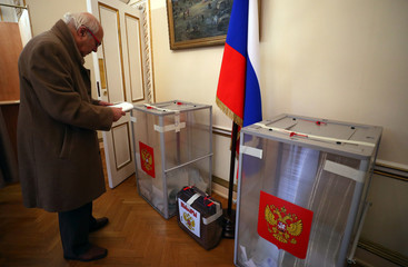 A man approaches a ballot box, during the presidential election, inside the Russian Embassy in London