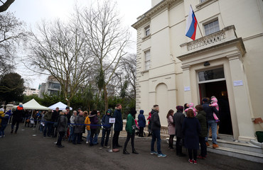People queue to cast their votes in the presidential election, outside the Russian Embassy in London