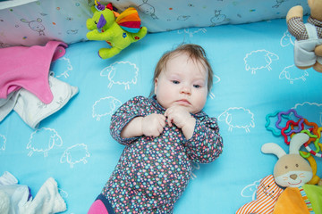 A cute baby is lying with toys in her crib.