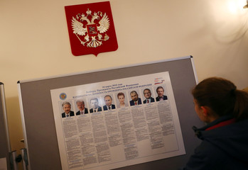 A woman looks at a list of candidates in the presidential election, inside the Russian Embassy in London