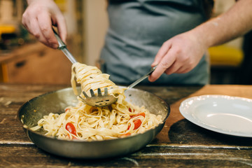 Chef cooking pasta, pan on wooden kitchen table