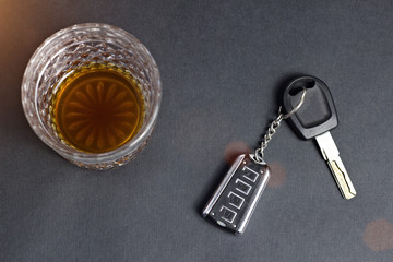 A glass with alcohol and car keys, the sun.