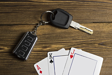 Playing cards and car keys on a wooden background