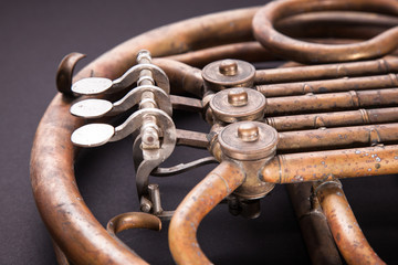Vintage bronze pipes, valve, key mechanical elements french horn, black background. Good pattern, prompt music instrument.