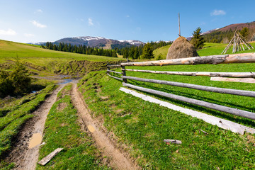 beautiful Carpathian countryside in springtime. dirt road down the hill and haystack behind the wooden fence. mountain ridge with snowy tops in the distance