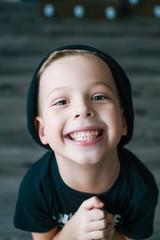 Portrait of an adorable young preschool boy in black cap.