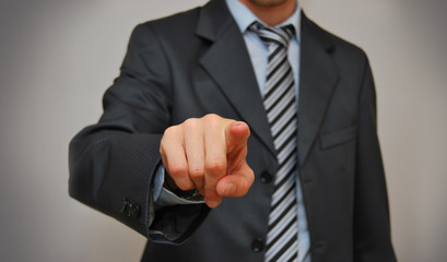 Businessman is touching futuristic screen with finger.