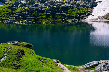 Belea lake in Fagarasan mountains of Romania. beautiful nature summer scenery with grassy slopes, rocky cliffs and some snow