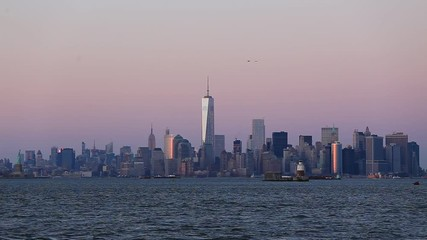 Fototapete - New York City Manhattan downtown skyline at dusk with skyscrapers illuminated over Hudson River panorama. Vertical composition, copy space.