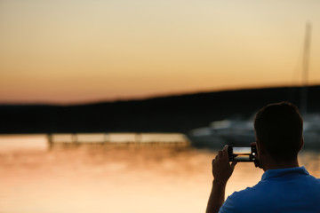 Man taking a picture from the shore. Using a smartphone to create a memory of beautiful sunset at the sea.