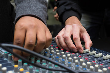 DJs Adjusting Sound on a Mixing Console.