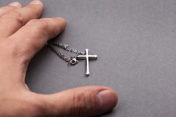 Silver cross in a hand