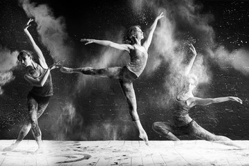 beautiful ballet dancer dancing barefoot on black background in a cloud of dust