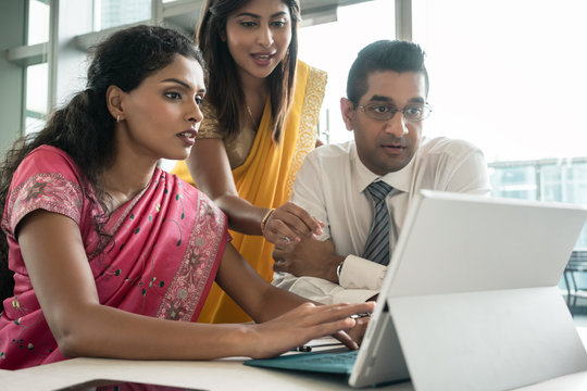 Three creative Indian employees working together around a laptop in a modern office