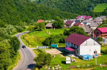 road through village in Carpathian mountains. bird eye view of beautiful rural scenery in summertime