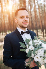 Portrait of a man in a suit with a bouquet of flowers in his hands