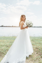 Bride in a white dress standing holding a wedding bouquet of flowers and greenery