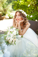 a young bride sits at a glass table with her hands folded at the chin