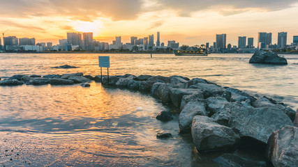 Sunset at the beach behind the city