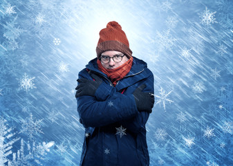 Boy freezing in warm clothing and snowing concept